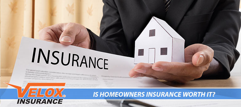 Insurance agent showing insurance policy and holding a home on his hand
